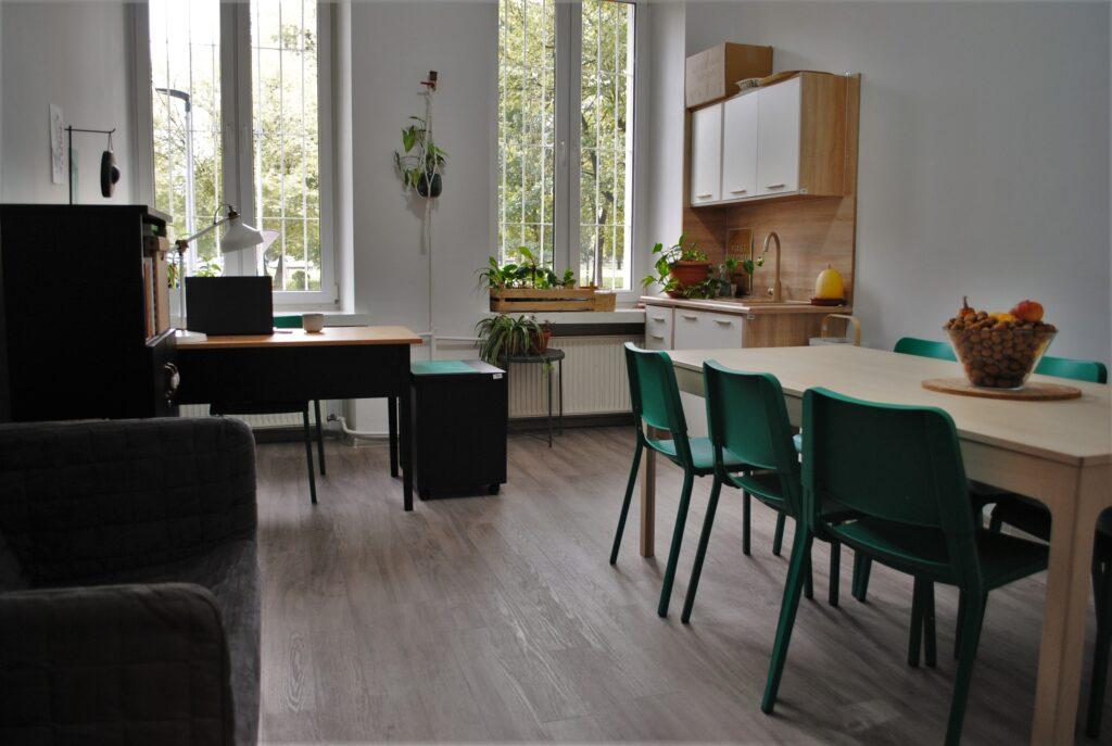 Pokój. Z prawej strony stoi stół i krzesła, z lewej strony kanapa. Na wprost od wejścia biurko i aneks kuchenny ze zlewem. W pomieszczeniu znajdują się dwa okna.